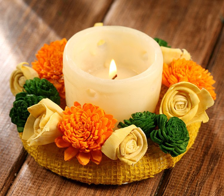 Candle surrounded by sola flowers- green-yellow-orange