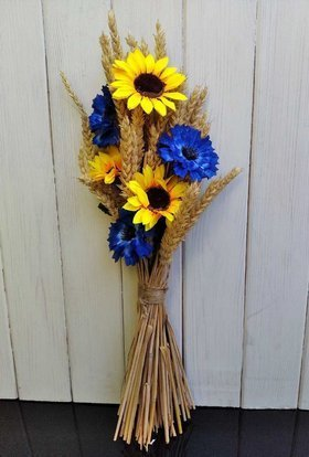 A bouquet of artificial flowers with ears of cereals, sunflowers and cornflowers