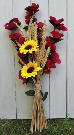 A bouquet of artificial poppy flowers, sunflowers and ears of grain