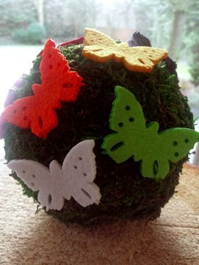 A moss ball decorated with butterflies.