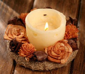 Candle surrounded by sola flowers- brown