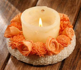 Candle surrounded by sola flowers- salmon pink