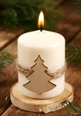 Christmas candle Candle with a Christmas tree on natural wood