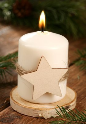Christmas candle, candle with a star on a wooden slice
